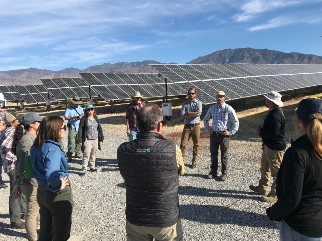 Group standing beside Nevada solar array.