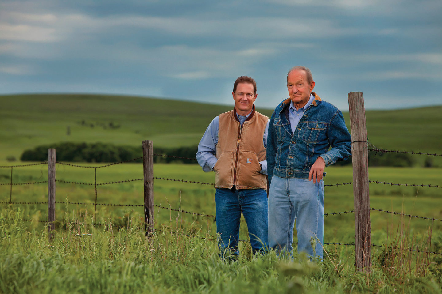 Two men standing in a field with a barbed wire fence behind them.